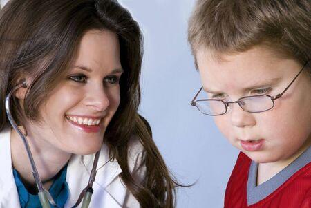stethoscope boy: A Female Pediatrician examining a young boy