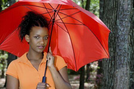 A beautiful young black woman holding an umbrella photo
