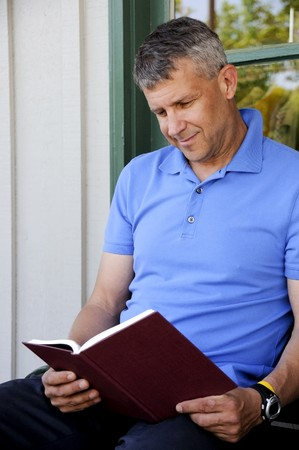 A handsome middle aged man reading a book photo