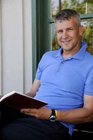 ハンサムな中年の男は本を読んで 写真素材