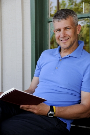 aged: A handsome middle aged man reading a book