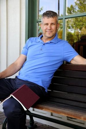 Een knappe man zittend op een bankje voor een gebouw