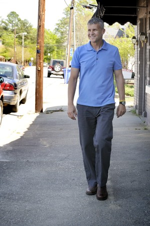 vecchiaia: Un uomo a piedi verso il basso un marciapiede accanto agli edifici