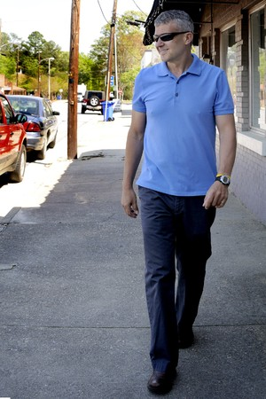 window shades: A Man Walking down a sidewalk next to buildings Stock Photo
