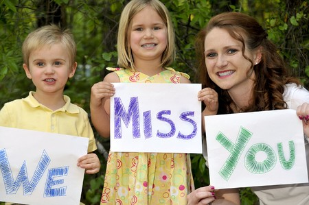 A single mom and her son and daughter holding signs photo