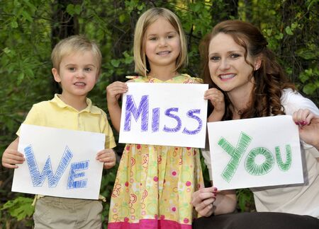 miss you: A single mom and her son and daughter holding signs