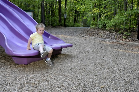 A young boy on a slide at a park Stock Photo - 6915448