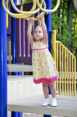 jungle gym: A little girl playing on a jungle gym