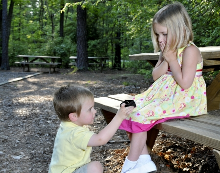 A little boy proposing marriage to a little girl  photo