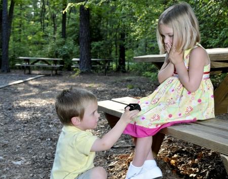 Een kleine jongen stelt huwelijk met een klein meisje