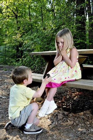 propose: A little boy proposing marriage to a little girl