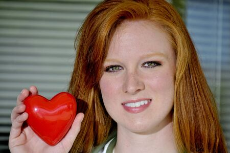 A female cardiologist holding a red heart Stock Photo - 7045313