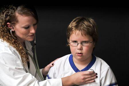 A Female Pediatrician examining a young boy