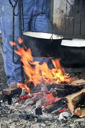 A cooking pot over a flaming campfire photo