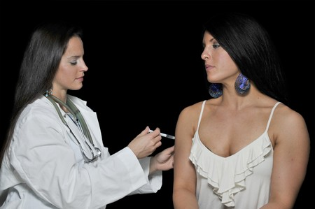 A female doctor giving a young woman a shot photo