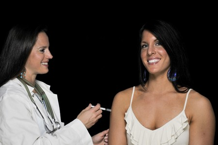 tetanus: A female doctor giving a young woman a shot Stock Photo