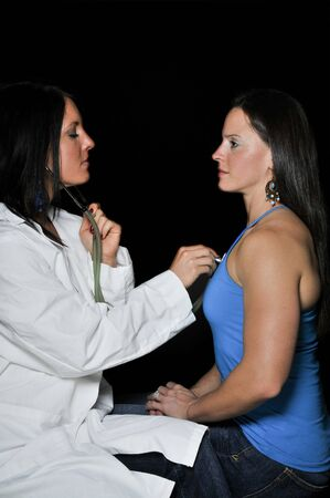 stethoscope: A beautiful young female doctor examaning a beautiful woman