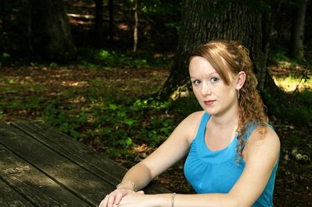 A beautiful woman sitting at a picnic table photo