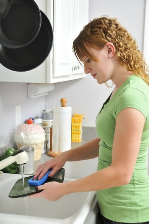 A woman doing the dishes after dinner. Stockfoto