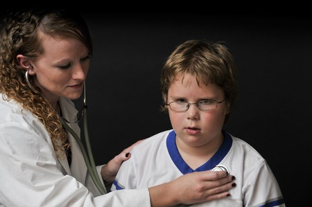 stethoscope: A Female Pediatrician examining a young boy