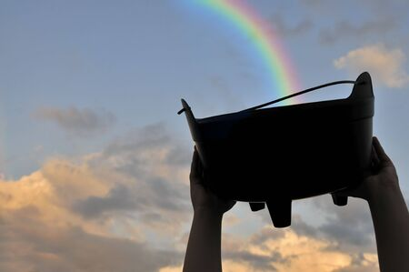 Collecting the treasure at the end of a rainbow Stock Photo