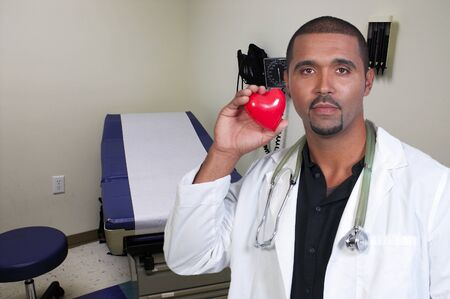 A male cardiologist holding a red heart photo