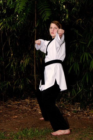 asian art: A young teenage girl practicing her Karate moves
