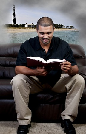 old furniture: A handsome black man reading a book Stock Photo