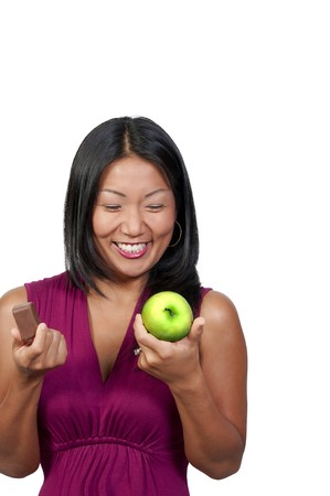 A woman trying to decide whether or not to eat healthy Imagens
