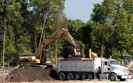 dumptruck: An industrial excavator filling up a dump truck Stock Photo