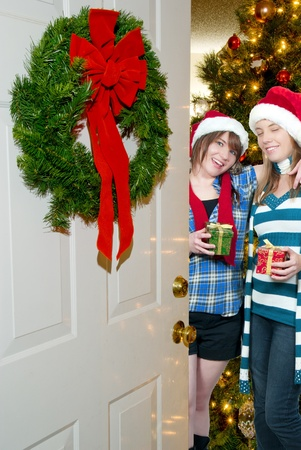 A couple of beautiful young women exchanging Christmas presents photo