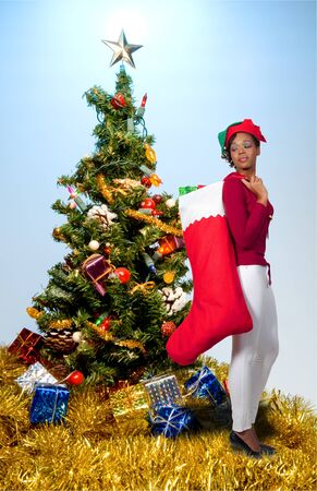 a beautiful woman elf holding a big Christmas stocking photo
