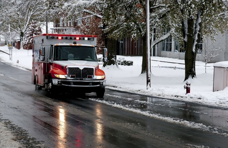 An ambulance driving to an emergency on a snow day photo
