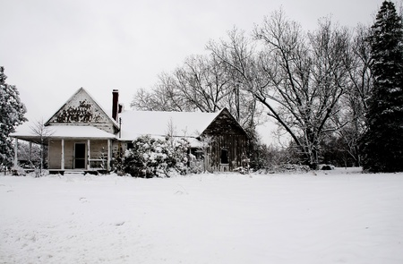 An old abandoned house covered in a winter blizzard snow storm photo