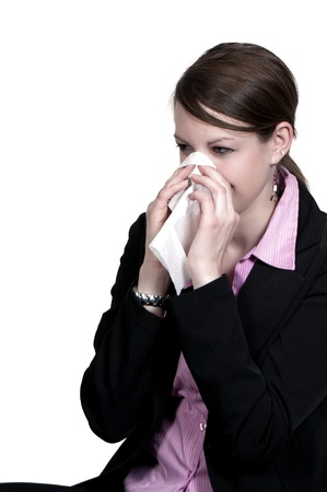 A beautiful woman with a cold, hay fever or allergies blowing her nose Stock Photo - 8672375