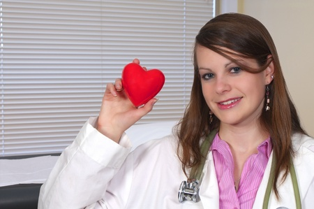 A female cardiologist office with a woman doctor holding a red heart in an exam room Stock Photo - 8671906