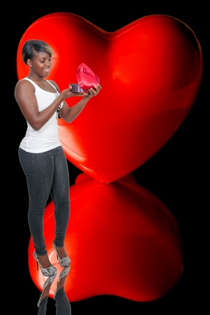 A beautiful young black African American woman holding a Valentines Day heart box gift present photo