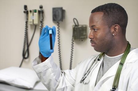 Een zwarte man Afrikaans Amerikaans arts holding een reageerbuis vial monster van bloed Stockfoto