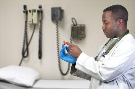 vacuna: Un hombre negro de doctor afroamericanos sosteniendo una jeringa Foto de archivo