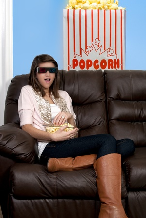 Beautiful young woman watching a 3d dvd movie on tv at home Stock Photo - 8891006