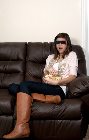 Beautiful young woman watching a 3d dvd movie on tv at home photo