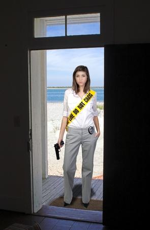 경찰관 테이프를 입고 권총을 들고 젊고 아름다운 여인 샷시로