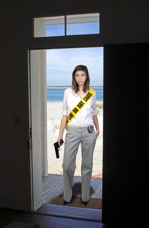 A young and beautiful woman holding a handgun wearing police line tape as a sash photo