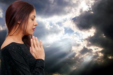 Beautiful Hispanic Latino Christian woman in deep prayer