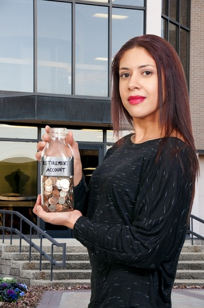 A beautiful Hispanic Latino woman holding her retirement account of coins in a milk bottle photo