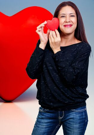 A beautiful young woman holding a Valentines Day heart photo