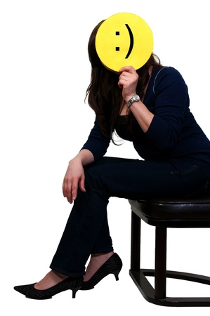 A beautiful depressed young woman hiding behind a smiley face photo