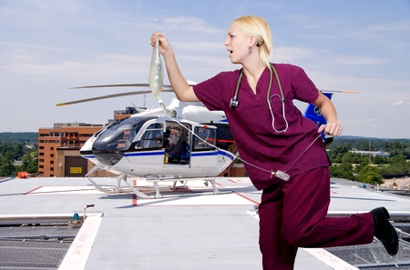 iv bag: A woman nurse running with an IV bag to a life flight helicopter ambulance