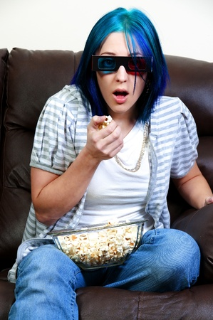 woman on couch: Beautiful young woman watching a 3d dvd movie on tv at home with popcorn
