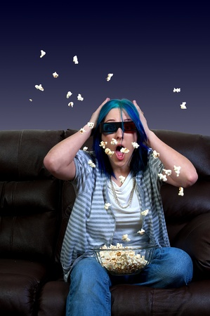 Beautiful young woman watching a 3d dvd movie on tv at home with popcorn photo